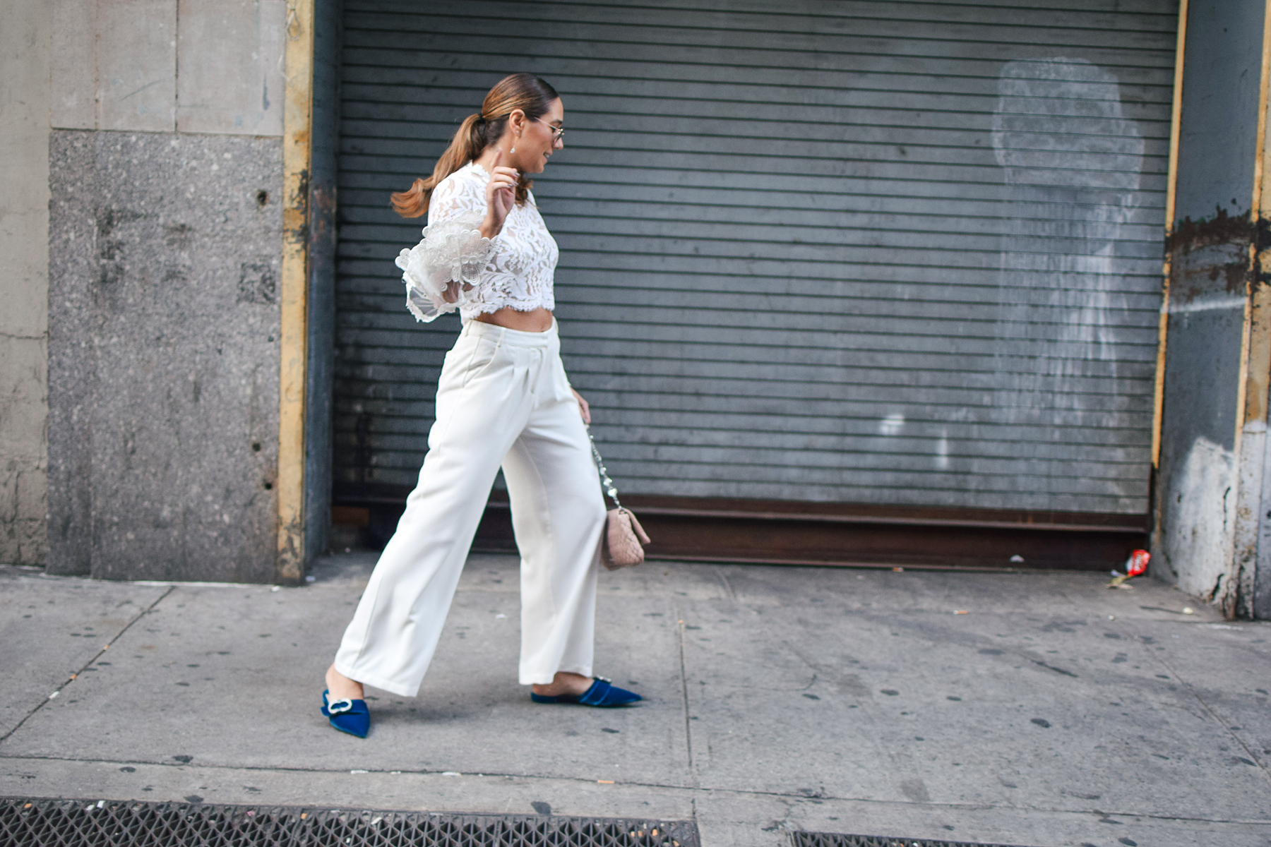 nyfw-streetstyle-outfit-lace-ruffle-statement-bell-sleeve-blouse-white-trousers-all-white-prada-royal-blue-slides-blush-accessories-candid-shot