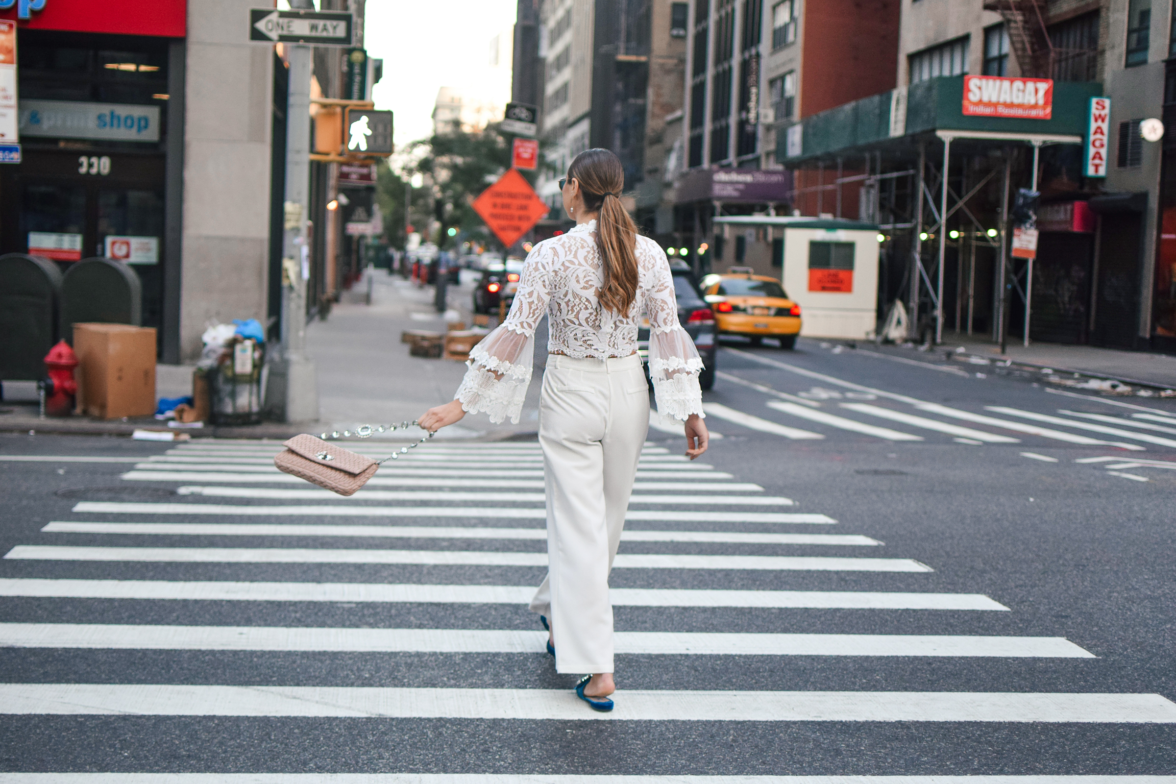 nyfw-streetstyle-outfit-lace-ruffle-statement-bell-sleeve-blouse-white-trousers-all-white-prada-royal-blue-slides-blush-accessories